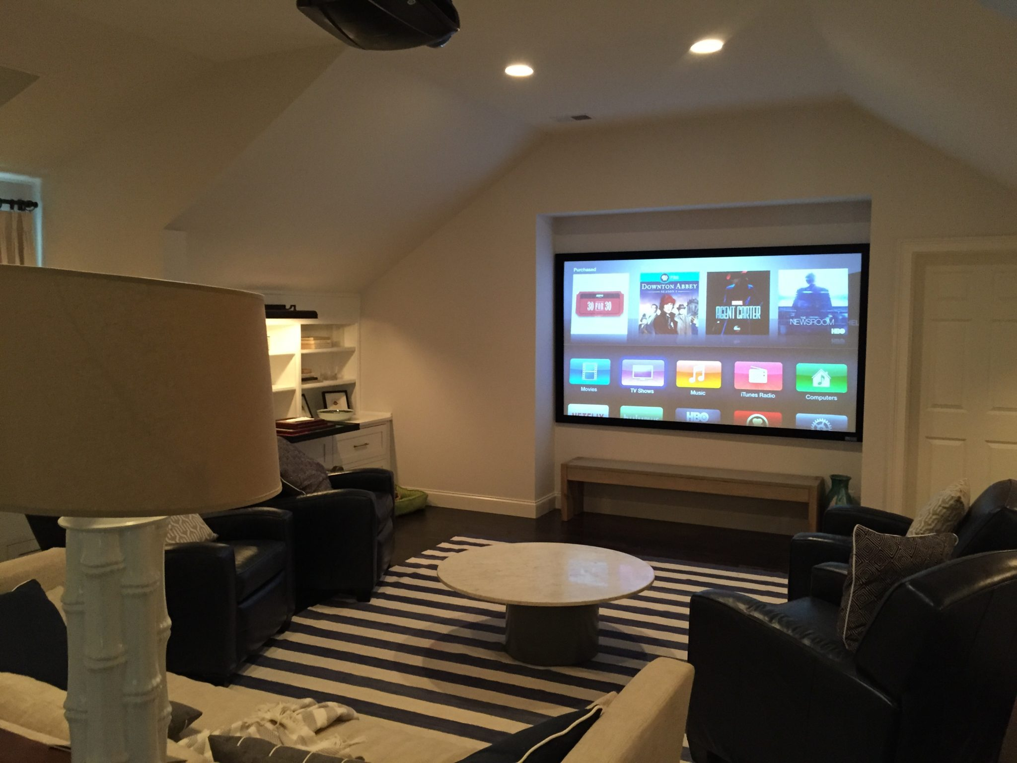 """110"""" acoustically transparent screen paired with a JVC 4K projector and 7.1 surround sound made up of Niles In-Wall speakers and Sunfire Subwoofers."""