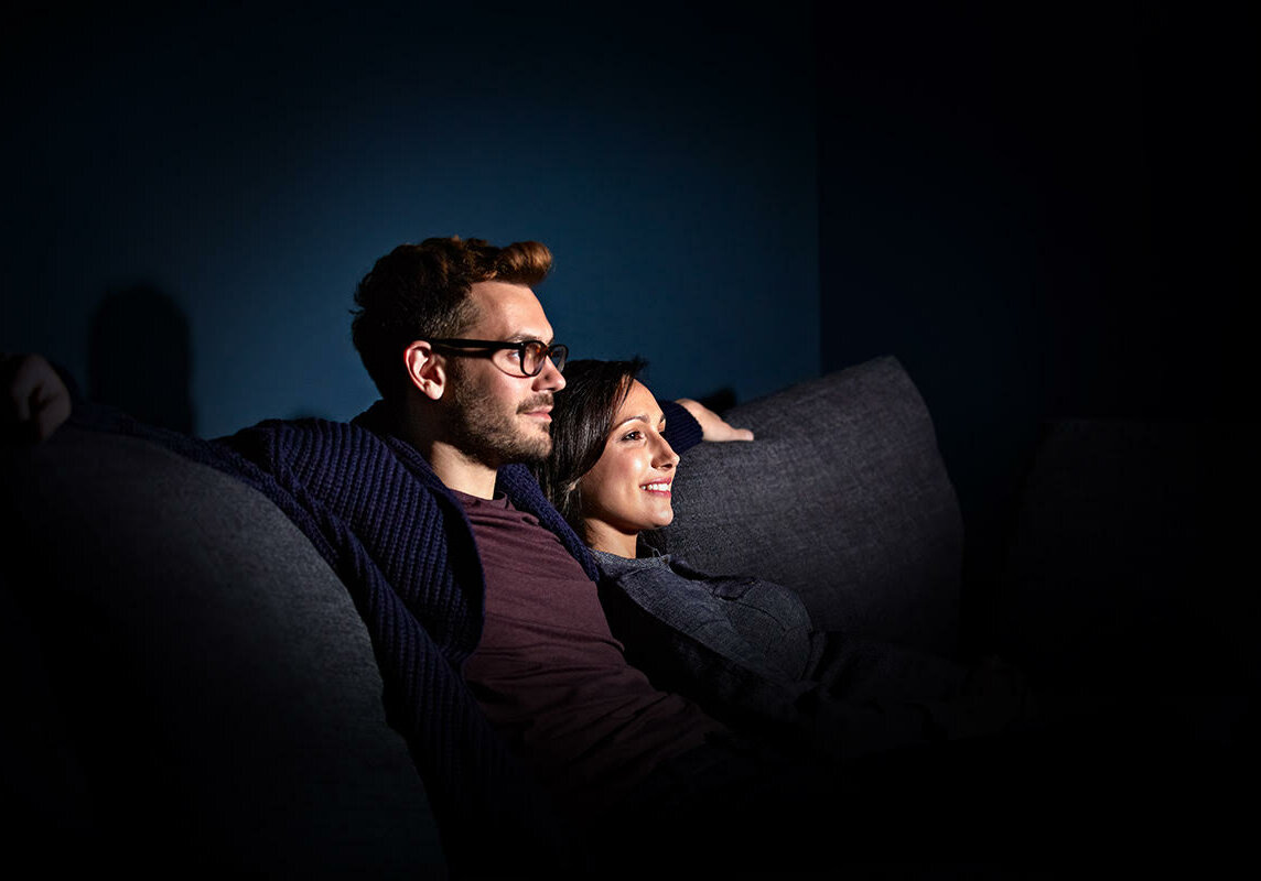 Shot of a pregnant woman and her husband sitting on the sofa watching television in the evening