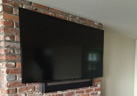 The Playbar and TV are mounted to a brick fireplace.